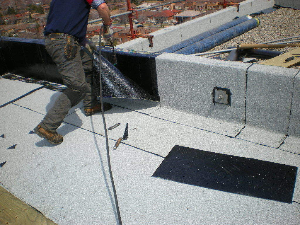 Contractor gluing down a roof membrane with a torch